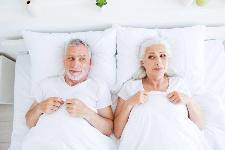 Casal de idosos na cama se olham com aparente vergonha ou timidez