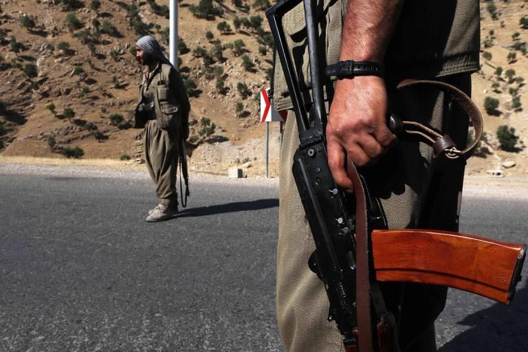 Dois combatentes de fuzil na mão em estrada