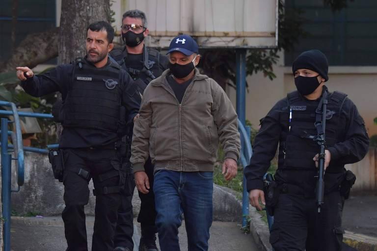 Fabrício Queiroz, de boné, é levado por policiais civis de SP após ter sido preso em Atibaia (SP)