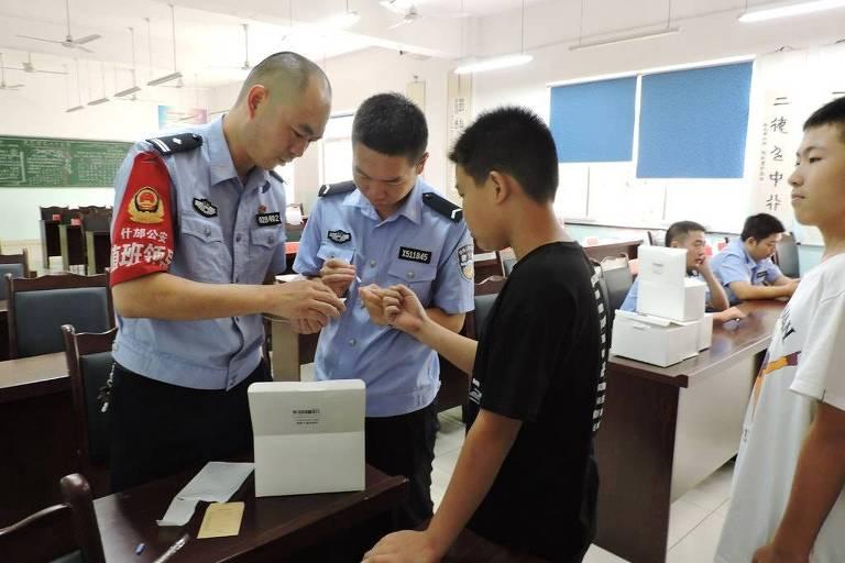 Policiais colhem amostras de DNA de meninos em escola na cidade de Shifang