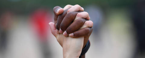 A man and a woman hold hands aloft in Hyde Park during a