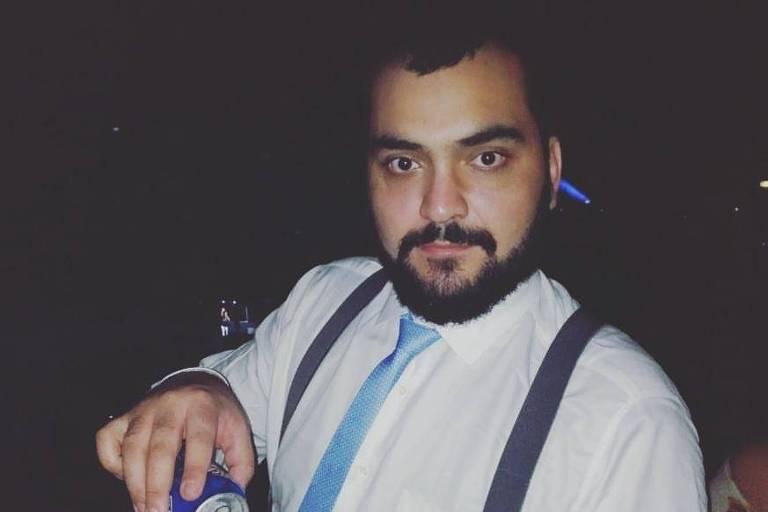 Luis vestido com gravata e suspensórios colocando uma cerveja no copo