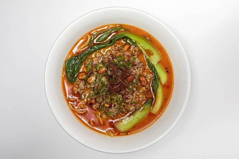 No tan tan men, o caldo de porco é temperado com pasta de pimenta e tahine e servido com copa lombo moída, acelga chinesa, cebolinha e shichimi togarashi