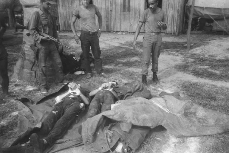 Na imagem em preto e branco, dois corpos aparecem no chão enquanto três pessoas observam