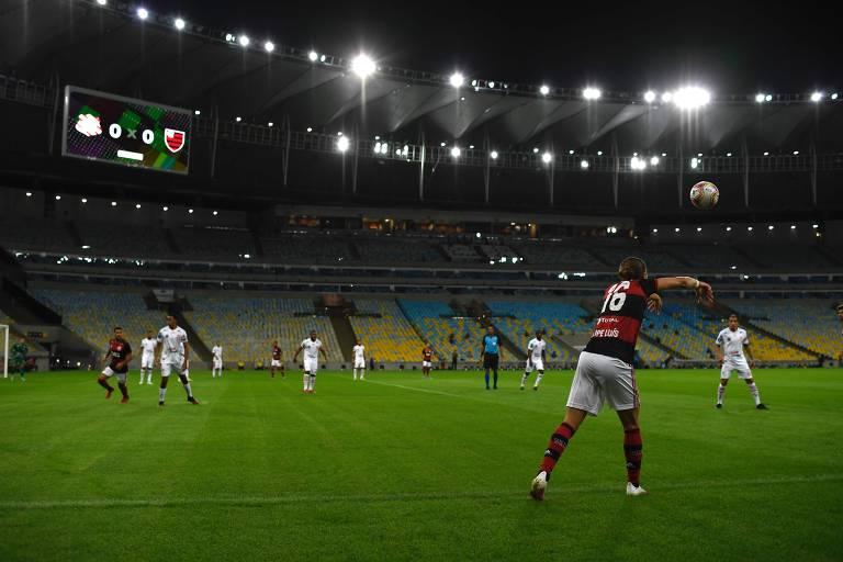Com as arquibancadas do Maracanã vazias ao fundo por causa da restrição de público, Filipe Luís, do Flamengo, cobra arremesso lateral