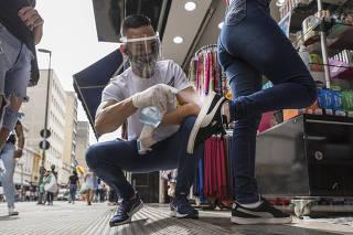 Reabertura gradual do comercio em Sao Paulo. Consumidores  recebem solucao desifentante no solado de seus calcados para entrar na loja Suprema Bijuterias na rua  25 de Marco no primeiro dia de reabertura gradual do comercio
