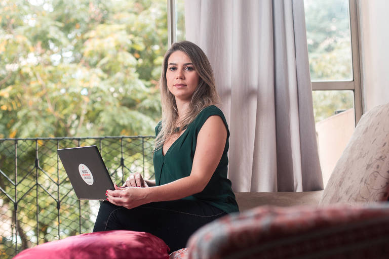 Mulher loira sentada em sacada com notebook no colo