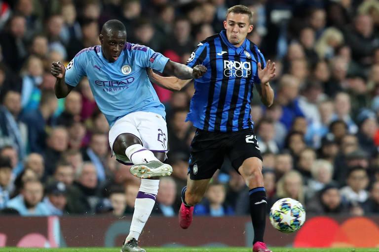 O brasileiro Rafael Tolói, da Atalanta, (à dir.) disputa bola com Benjamin Mendy, do Manchester City, em partida entre as duas equipes pela Champions League