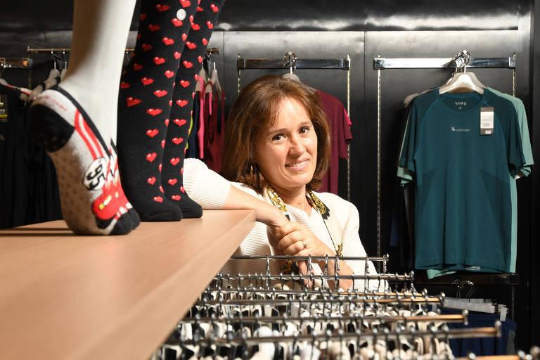 Isabelle apoiada em uma prateleira de loja com meias