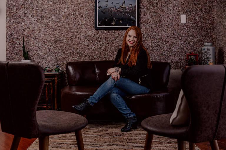 Mulher ruiva sentada em sofá preto, com as pernas cruzadas
