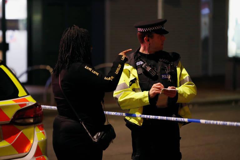 Mulher conversa com policial no local onde três pessoas foram mortas em Reading, na Inglaterra
