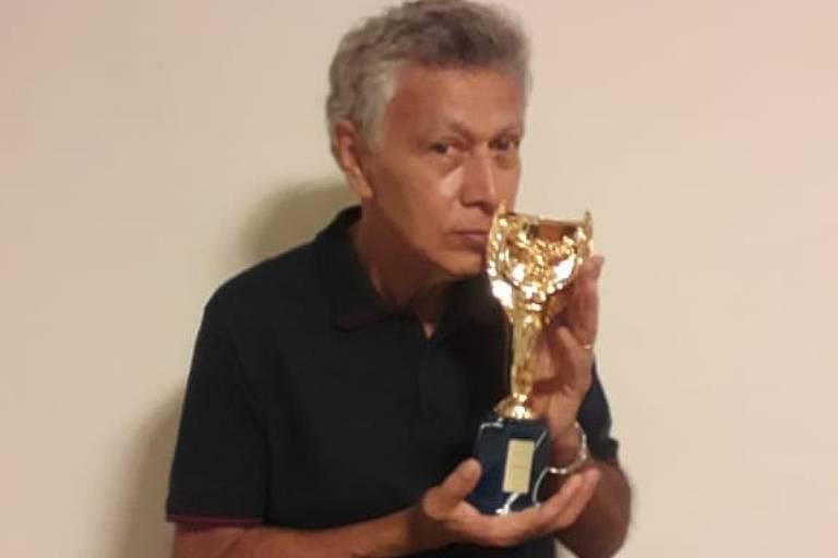 O ex-volante da seleção brasileira Clodoaldo, tricampeão na Copa do Mundo no México em 1970, beija a réplica da taça Jules Rimet