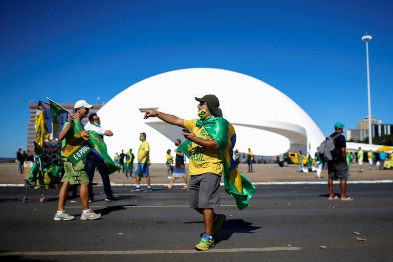 Manifestantes estão no meio da rua, usam camisetas amarelas e seguram bandeiras do Brasil