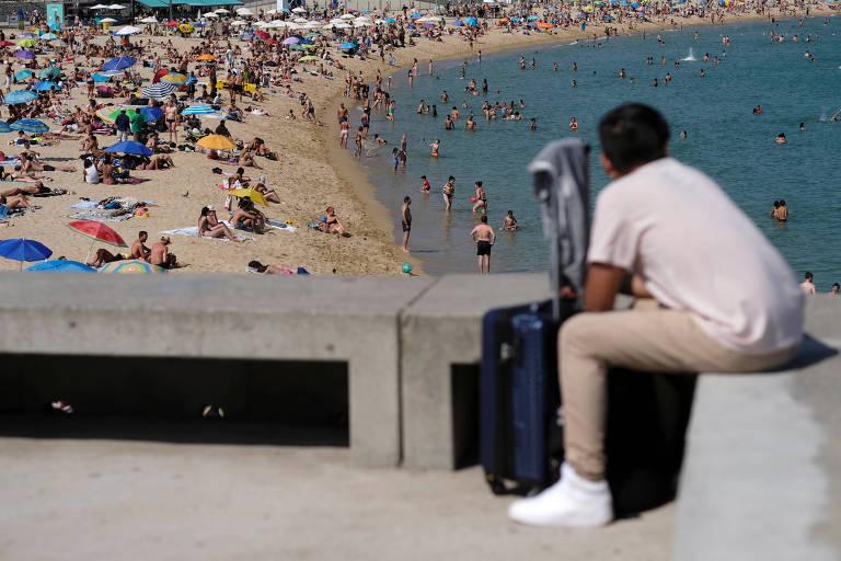 homem olha gente na praia