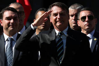 FILE PHOTO: Brazilian President Jair Bolsonaro and his son and Senator Flavio Bolsonaro attend a ceremony to celebrate the 130th anniversary of the Military School in Rio de Janeiro