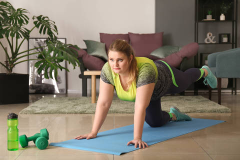 Beautiful plus size girl training at home. Concept of body positivity