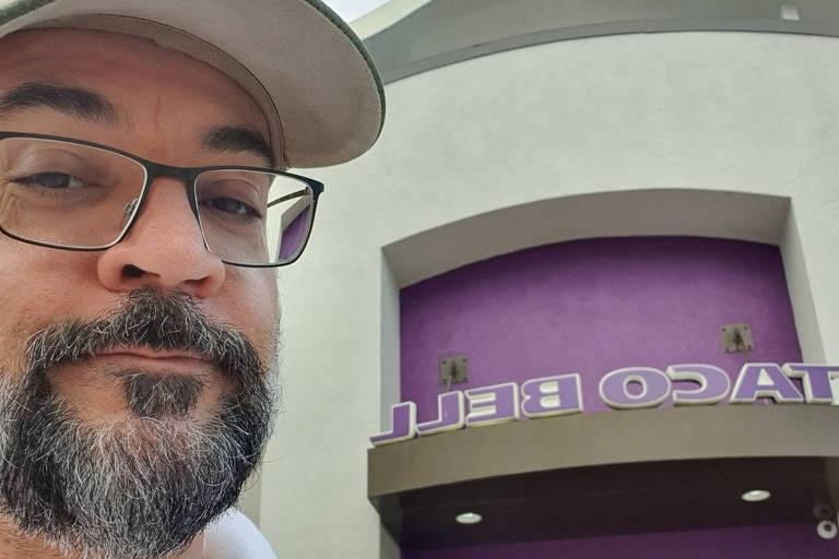 Homem de barba e boné com fachada de restaurante ao fundo