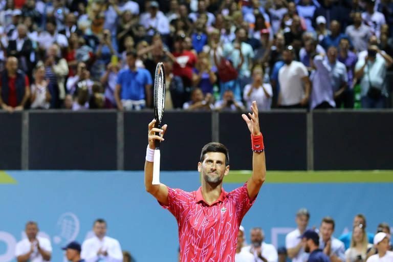 Djokovic cumprimenta o público com as mãos para o alto; atrás dele, arquibancada cheia de espectadores