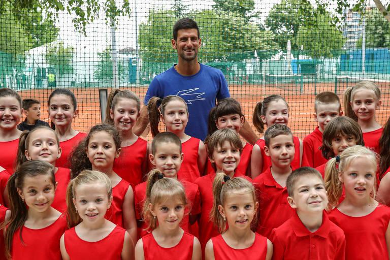 Dezenas de crianças posam para foto em frente a Djokovic
