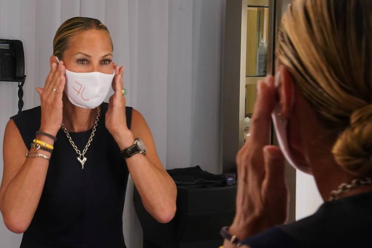Mulher ajusta máscara no primeiro dia da fase dois de reabertura em Nova York, que permitiu a retomada de salões de beleza