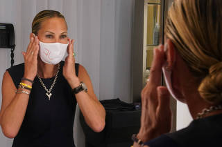 Suelyn Farel adjusts her mask on the first day of the phase two re-opening of businesses following the outbreak of the coronavirus disease (COVID-19), in the Manhattan borough of New York City