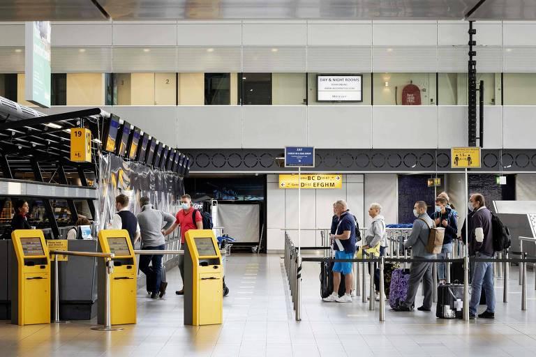 Passageiros aguardam em fila para fazer check-in no aeroporto Schiphol, em Amsterdã