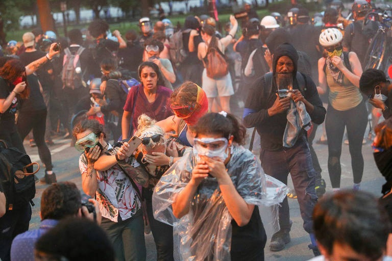 Manifestantes reagem ao efeito de spray de pimenta atirado pela polícia no Lafayette Park, em Washington