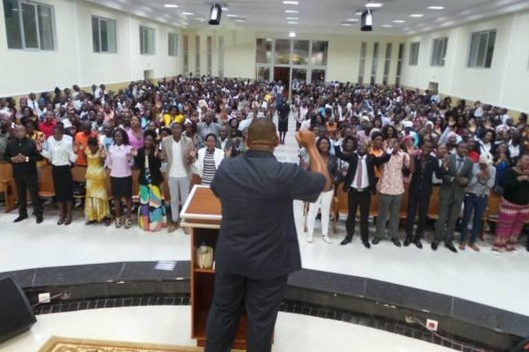pastor visto de costas; à frente dele, grupo de fiéis ora com as mãos dadas