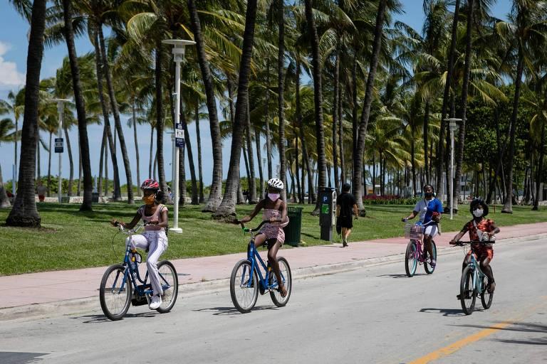 Pessoas andam de bicicleta em praia de Miami, na Flórida; estado enfrenta alta de casos de coronavírus