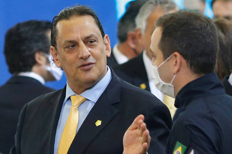 Wassef de terno gesticula ao falar com um homem que aparece ao seu lado, de máscara