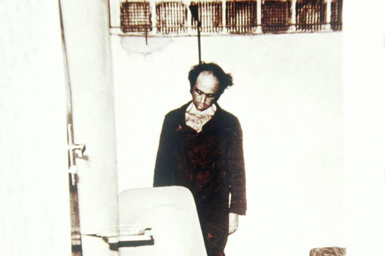 Na imagem em preto e branco, o jornalista Vladimir Herzog aparece enforcado. A corda que está em seu pescoço aparece amarrada a grade de uma janela a poucos metros do chão. Na frente dele, há uma cadeira.