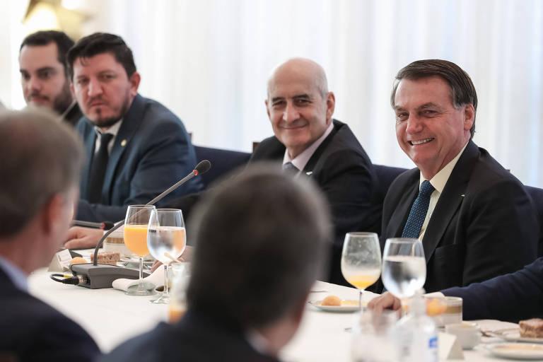 Bolsonaro sorrindo à mesa com ministro e parlamentares
