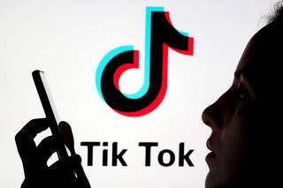 FILE PHOTO: A person holds a smartphone as Tik Tok logo is displayed behind in this picture illustration