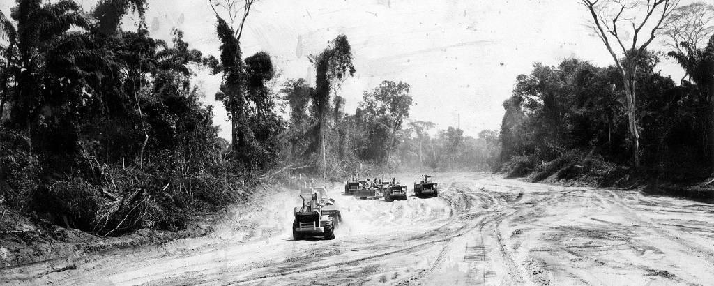 Na imagem em preto e branco, tratores estão em uma estrada de terra fazem terraplanagem em trecho da rodovia Transamazônica em Manaus, no Amazonas. Ao redor da estrada há vegetação.
