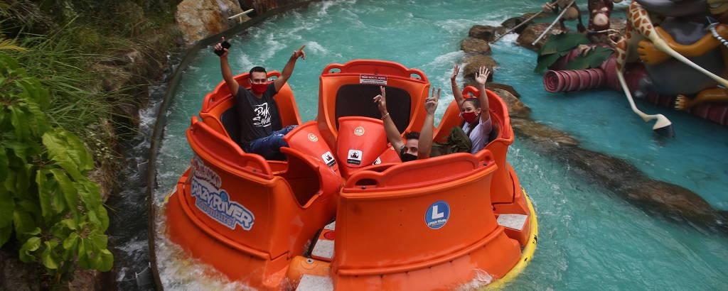 Três pessoas com máscaras em bote laranja em rio artificial