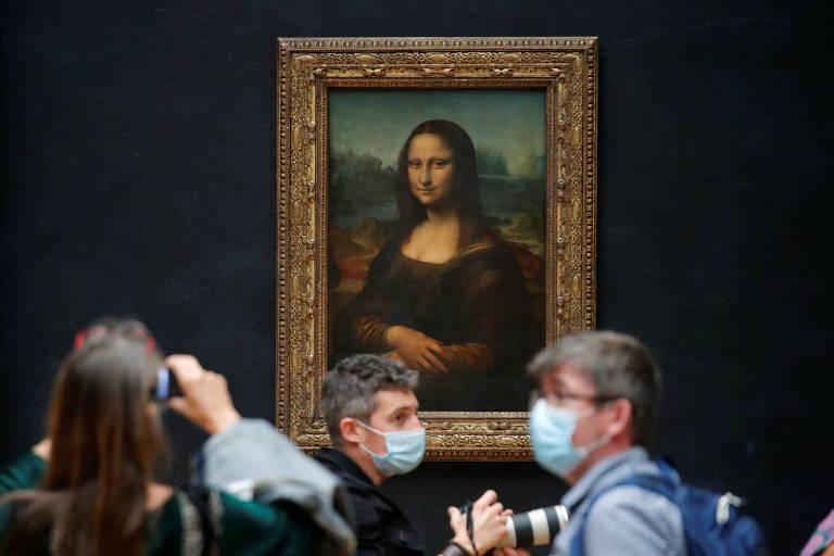 Pessoas com máscara em frente à quadro de Mona Lisa