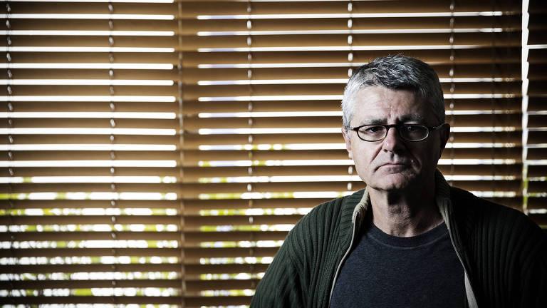 Homem de camiseta preta e casaco verde, de óculos, na frente de uma janela