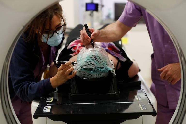 Profissionais de saúde colocam máscara termoplástica em paciente no centro de câncer San Pietro, em Roma