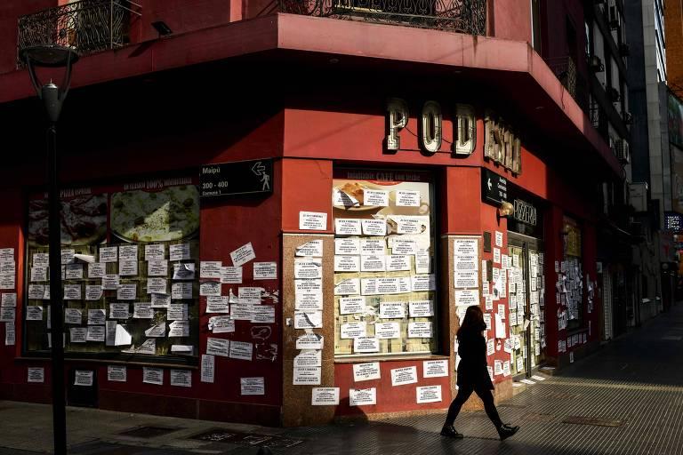 Mulher caminha em frente a fachada de pizzaria fechada e coberta com relcamações de ex-funcionários em Buenos Aires