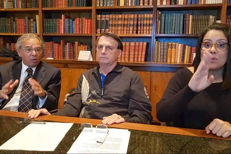 Paulo Guedes e intérprete de libras gesticulam, enquanto Bolsonaro olha para frente