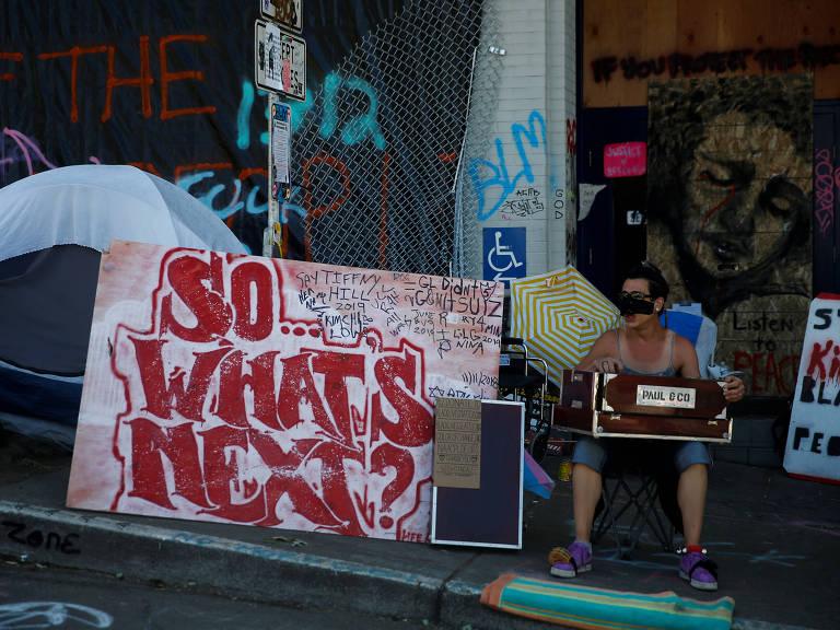 Placa com os dizeres 'Então... o que acontece agora?' ao lado de delegacia da polícia de Seattle, em espaço ocupado por ativistas que protestam contra a violência policial e o racismo