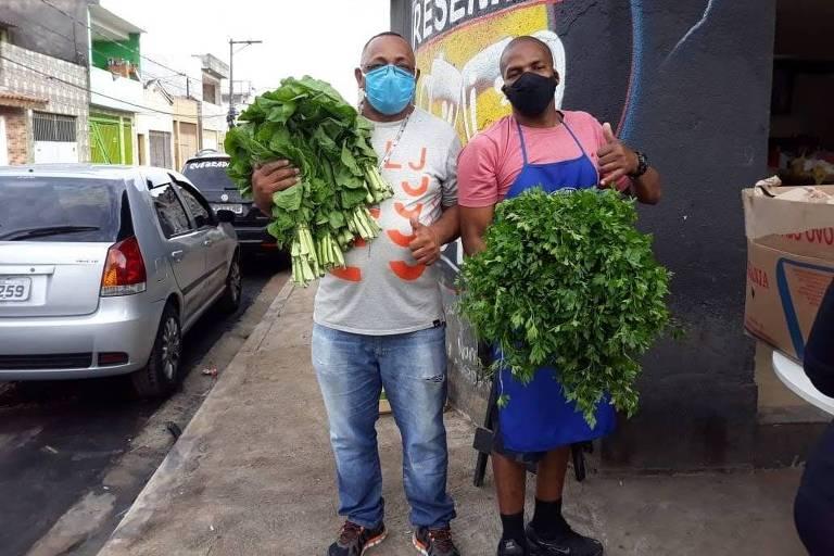 Eriosvaldo Silva e José Júnior em frente ao bar onde ocorre a distribuição dos alimentos (Weslley Galzo/Agência Mural)