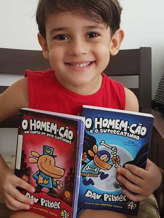 Menino veste regata vermelha e sorri com dois livros da série em suas mãos