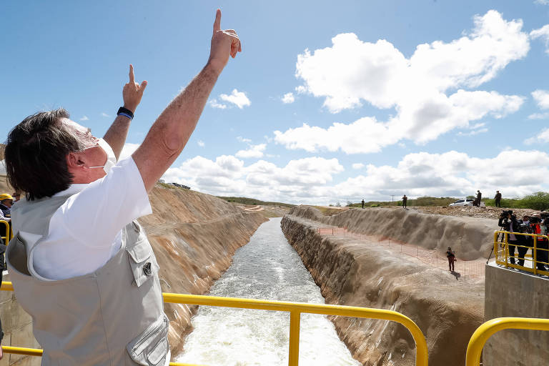 Bolsonaro, diante do Rio, erguendo as duas mãos para o céu
