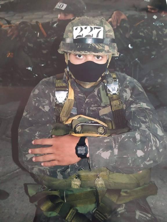 Soldado com roupa camuflada, capacete e máscara