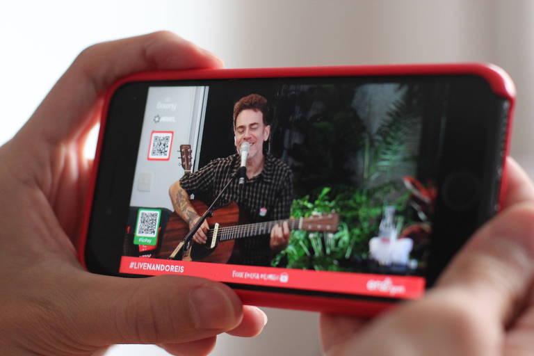 Mãos segurando Smartphone enquanto celular passa live do cantor Nando Reis
