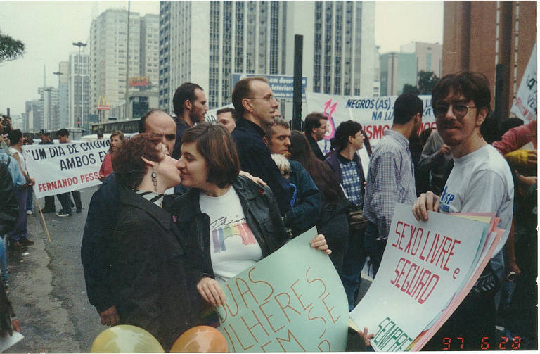Duas mulheres se beijam segurando cartaz anti-homofobia