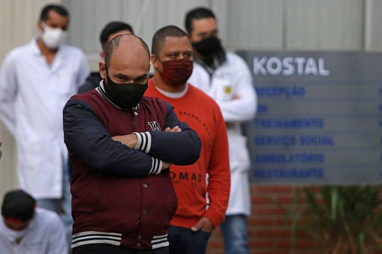 Trabalhadores de máscara para se proteger da covid-19 cruzam os braços em frente a uma placa escrita Kostal