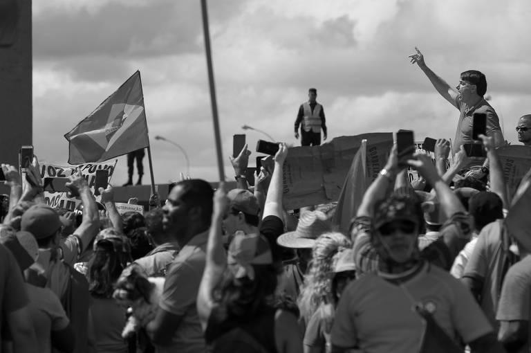 O presidente Jair Bolsonaro cumprimenta e discursa para apoiadores em cima de uma caçamba de caminhonete frente do quartel-general do Exército, em Brasília (DF)