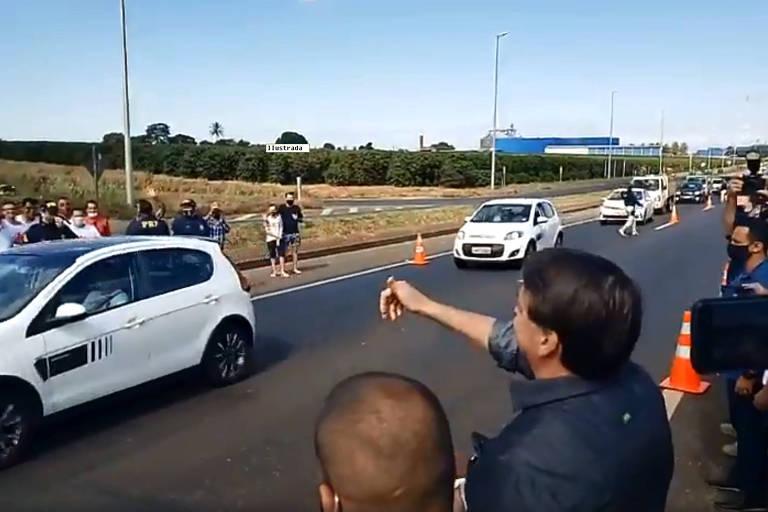 Bolsonaro acena a simpatizantes à beira de rodovia, sem máscara de proteção